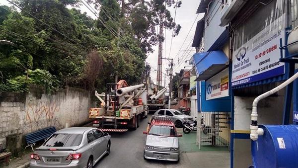 Carros e caminhão da Eletropaulo na contramão na Estrada Velha de Cotia, na Granja Viana