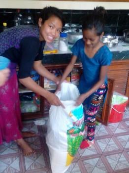 Nepalesa que está ajudando a ONG e um saco de alimentos doados