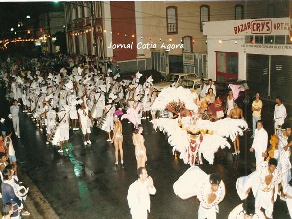 1986: Ala das baianas desfilando em frente à Praça da Matriz e o Bazar Crys ao fundo